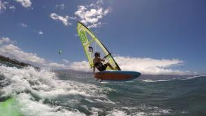 Dax Barker jumps over a wave on Maui